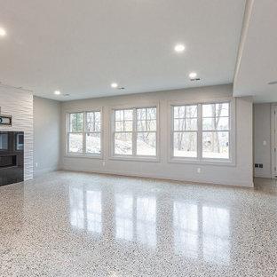 Exemple d'un très grand sous-sol chic donnant sur l'extérieur avec un mur blanc, un sol en marbre, une cheminée standard et un sol beige.