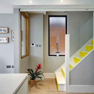 Large contemporary walk-out basement in London with grey walls and medium hardwood flooring.