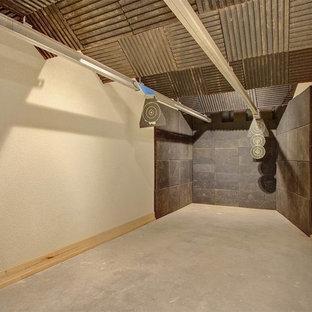 Inspiration pour un grand sous-sol chalet donnant sur l'extérieur avec un mur marron, une cheminée standard et un manteau de cheminée en pierre.