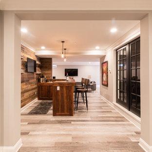 Cette image montre un grand sous-sol chalet enterré avec un bar de salon, un mur gris, un sol gris et du lambris de bois.