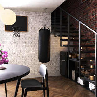 This is an example of a medium sized urban walk-out basement in London with no fireplace, brown floors and dark hardwood flooring.