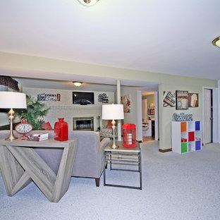 Inspiration pour un sous-sol traditionnel semi-enterré et de taille moyenne avec un mur beige, moquette, une cheminée standard, un manteau de cheminée en brique et un sol gris.