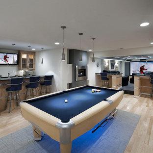 Réalisation d'un sous-sol design enterré avec un mur gris, un sol en bois clair, un sol beige et salle de jeu.