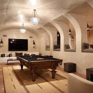 Cette image montre un sous-sol méditerranéen avec un mur beige, un sol en carreau de terre cuite, un sol orange et salle de jeu.