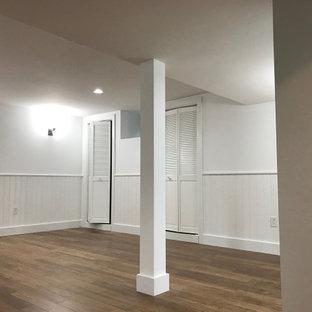Exemple d'un sous-sol tendance enterré et de taille moyenne avec un bar de salon, un sol en bambou, un manteau de cheminée en plâtre et boiseries.