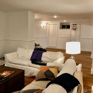 Idée de décoration pour un sous-sol design enterré et de taille moyenne avec un bar de salon, un sol en bambou, un manteau de cheminée en plâtre et boiseries.