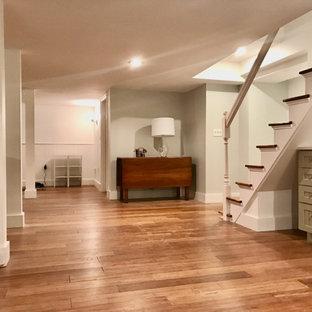 Cette image montre un sous-sol design enterré et de taille moyenne avec un bar de salon, un sol en bambou, un manteau de cheminée en plâtre et boiseries.