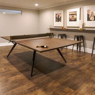 Idée de décoration pour un sous-sol tradition enterré avec un mur gris, un sol en vinyl, une cheminée double-face, un manteau de cheminée en bois et un sol marron.