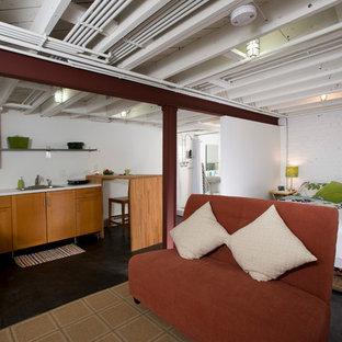 Aménagement d'un grand sous-sol classique donnant sur l'extérieur avec un mur blanc, béton au sol, aucune cheminée et un sol noir.