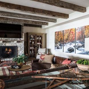 Idée de décoration pour un grand sous-sol tradition donnant sur l'extérieur avec un mur beige, un sol en calcaire, une cheminée standard et un manteau de cheminée en pierre.