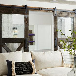 Idéer för en mellanstor lantlig källare ovan mark, med vita väggar, heltäckningsmatta, en öppen hörnspis, en spiselkrans i sten och grått golv