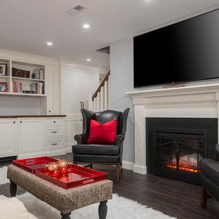 Idée de décoration pour un petit sous-sol tradition donnant sur l'extérieur avec un mur gris, un sol en vinyl, une cheminée standard et un manteau de cheminée en pierre.