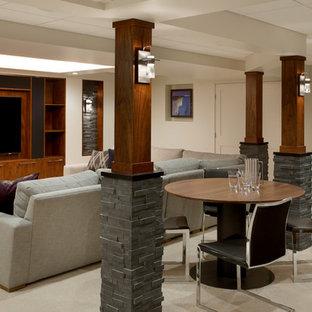 Cette image montre un grand sous-sol traditionnel enterré avec un mur beige, moquette, une cheminée standard et salle de cinéma.