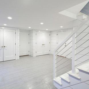 Cette image montre un sous-sol marin donnant sur l'extérieur et de taille moyenne avec un mur blanc, un sol gris, un sol en ardoise et aucune cheminée.