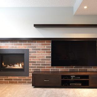 Réalisation d'un grand sous-sol design semi-enterré avec moquette, une cheminée standard, un manteau de cheminée en brique, un mur gris et un sol beige.