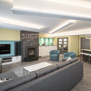 Exemple d'un sous-sol tendance donnant sur l'extérieur et de taille moyenne avec un mur vert, un sol en bois foncé, un poêle à bois, un manteau de cheminée en carrelage et un sol gris.