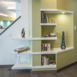 Inspiration pour un sous-sol design donnant sur l'extérieur et de taille moyenne avec un mur vert, un sol en bois foncé, un poêle à bois, un manteau de cheminée en carrelage et un sol gris.