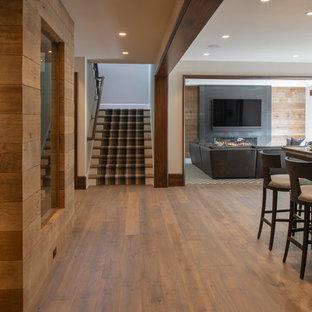 Cette photo montre un grand sous-sol montagne donnant sur l'extérieur avec un mur blanc, un sol en bois brun, une cheminée standard, un manteau de cheminée en métal et un sol marron.
