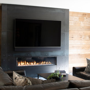 Exemple d'un grand sous-sol montagne donnant sur l'extérieur avec un mur blanc, un sol en bois brun, une cheminée standard, un manteau de cheminée en métal et un sol marron.