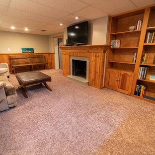Inspiration pour un sous-sol donnant sur l'extérieur et de taille moyenne avec un mur gris, un sol en bois brun, une cheminée standard, un manteau de cheminée en bois et un sol orange.