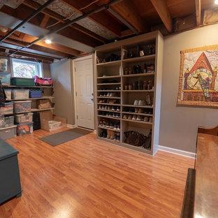 Aménagement d'un sous-sol donnant sur l'extérieur et de taille moyenne avec un mur gris, un sol en bois brun, aucune cheminée et un sol orange.