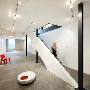 Inspiration pour un petit sous-sol minimaliste semi-enterré avec un mur blanc, béton au sol, aucune cheminée et un sol gris.
