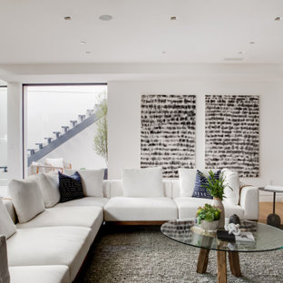 Design ideas for a midcentury walk-out basement in Los Angeles with white walls and light hardwood floors.