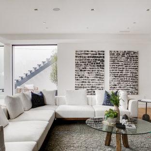 Aménagement d'un sous-sol rétro donnant sur l'extérieur avec un mur blanc et un sol en bois clair.