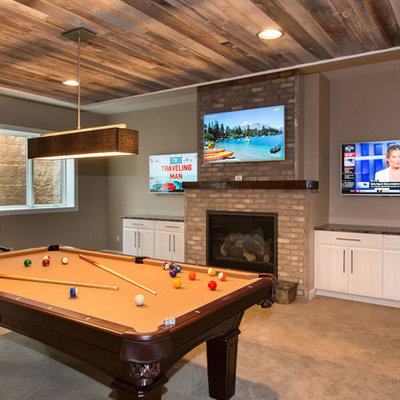 Mid-sized transitional underground carpeted basement photo in Other with beige walls, a standard fireplace and a brick fireplace