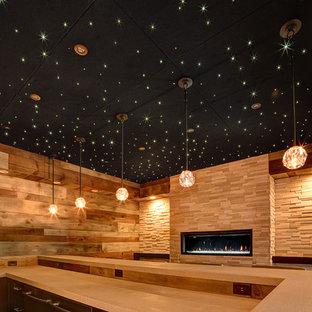 Großes Stilmix Souterrain mit beiger Wandfarbe, braunem Holzboden, Kamin und Kaminumrandung aus Stein in Sonstige
