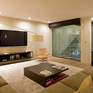 Idées déco pour un sous-sol moderne semi-enterré et de taille moyenne avec un mur beige, un sol en bois clair et un sol marron.