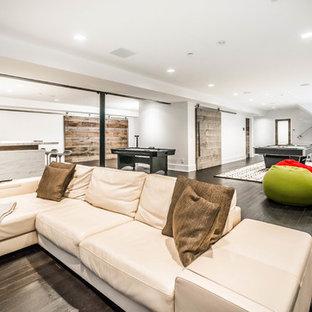 Idée de décoration pour un grand sous-sol minimaliste semi-enterré avec un mur blanc, un sol en bois foncé, une cheminée standard et un manteau de cheminée en carrelage.