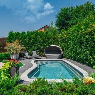 """Ispirazione per una piscina contemporanea a """"C"""" nel cortile laterale con pedane"""
