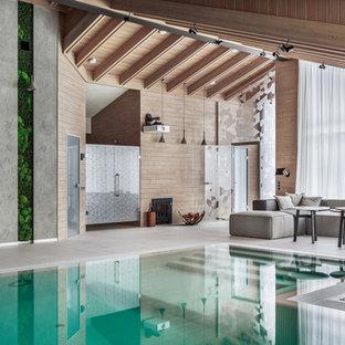 Идея дизайна: огромный спортивный бассейн произвольной формы в доме в современном стиле с домиком у бассейна