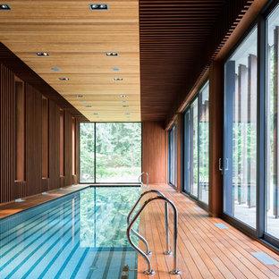Пример оригинального дизайна: прямоугольный бассейн в доме в современном стиле с настилом