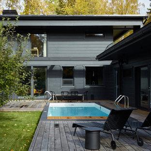 Пример оригинального дизайна: прямоугольный бассейн на боковом дворе в современном стиле с настилом