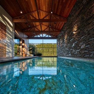 На фото: элитные прямоугольные бассейны среднего размера в доме в современном стиле с дорожками из брусчатки из камня