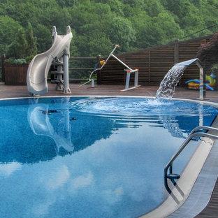 Imagen de piscina con tobogán elevada, contemporánea, de tamaño medio, tipo riñón, en patio, con entablado