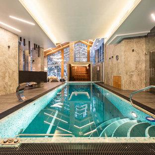 Пример оригинального дизайна интерьера: прямоугольный бассейн в доме в современном стиле с настилом