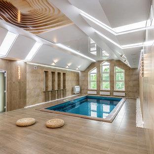 Новые идеи обустройства дома: прямоугольный бассейн в доме в современном стиле с покрытием из плитки