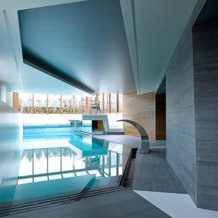 На фото: спортивный бассейн произвольной формы в доме в современном стиле с