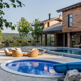 На фото: круглый бассейн на боковом дворе в современном стиле с водной горкой