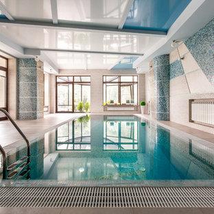 На фото: прямоугольный бассейн в доме в современном стиле с домиком у бассейна