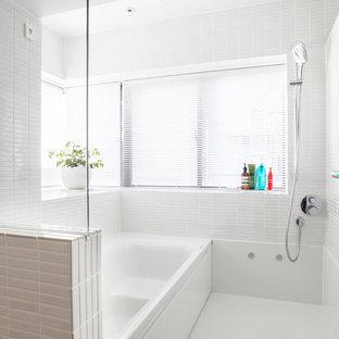 Imagen de cuarto de baño principal, moderno, pequeño, con bañera empotrada, combinación de ducha y bañera, baldosas y/o azulejos blancos, azulejos en listel, paredes blancas y suelo de baldosas de cerámica