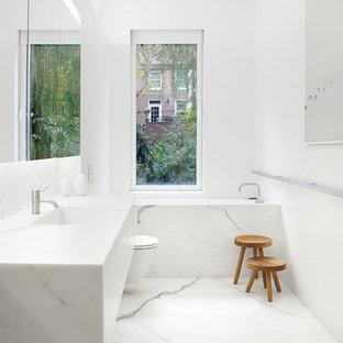 Idee per una stanza da bagno padronale moderna di medie dimensioni con WC sospeso, pareti bianche, pavimento in marmo, lavabo integrato, top in marmo, vasca ad alcova e piastrelle di marmo