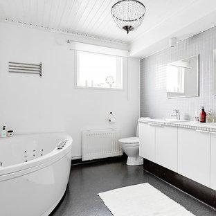Esempio di una grande stanza da bagno padronale nordica con ante a filo, ante bianche, vasca ad angolo, doccia alcova, WC monopezzo, piastrelle bianche, pareti bianche, lavabo da incasso e top piastrellato