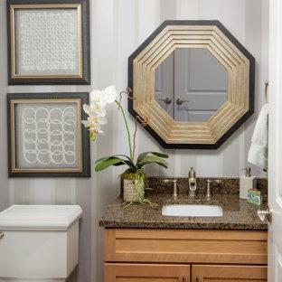 Imagen de cuarto de baño con ducha y papel pintado, moderno, pequeño, con puertas de armario marrones, sanitario de una pieza, paredes grises, lavabo encastrado, encimera de granito y encimeras marrones