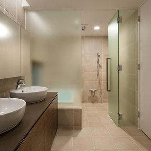 Inredning av ett modernt badrum, med en kantlös dusch, beige väggar, ett fristående handfat, släta luckor, bruna skåp, ett badkar i en alkov, rosa kakel och beiget golv