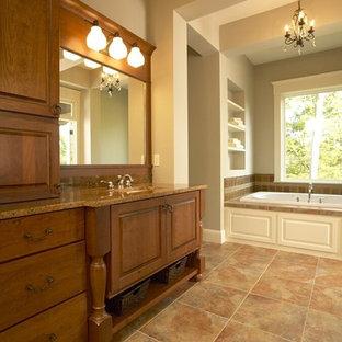 Immagine di una grande stanza da bagno padronale chic con ante con bugna sagomata, ante in legno bruno, vasca da incasso, pareti beige, pavimento con piastrelle in ceramica, lavabo sottopiano, top in granito e pavimento beige