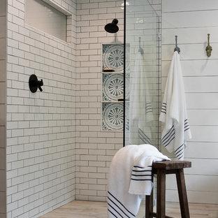 Lantlig inredning av ett mellanstort svart svart en-suite badrum, med möbel-liknande, skåp i mörkt trä, ett fristående badkar, en kantlös dusch, vit kakel, tunnelbanekakel, vita väggar, ljust trägolv, ett undermonterad handfat, beiget golv och med dusch som är öppen